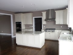 Kitchen with large island, hardwood floors, and opening to dining room