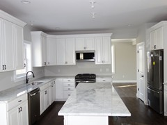 Kitchen with large central island and standard stainless steel GE Appliances.